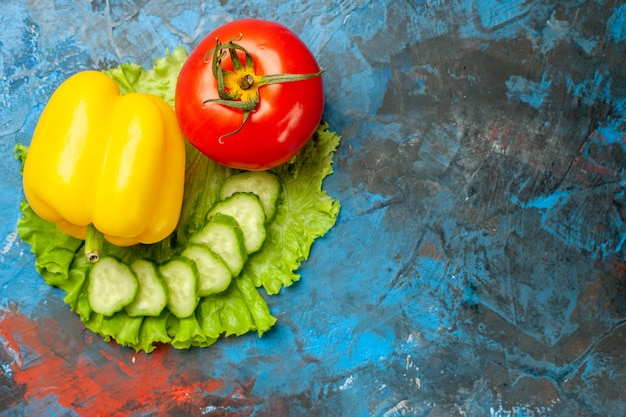 Bovenaanzicht verse groenten komkommer tomaat groene salade en knoflook op blauwe achtergrond