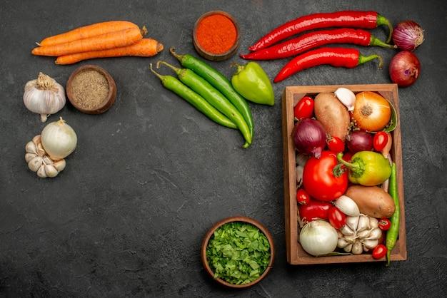 Bovenaanzicht verse groenten met greens en knoflook op de donkere tafel rijpe salade kleur gezondheid