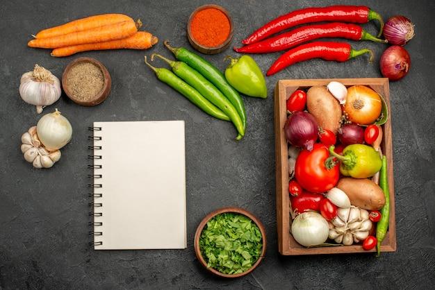 Bovenaanzicht verse groenten met greens en knoflook op donkere bureau rijpe salade kleur gezondheid