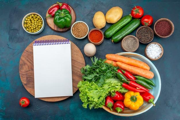 Bovenaanzicht verse groenten met greens en kruiden op de blauwe groente van de de lunchsalade van de bureausnack