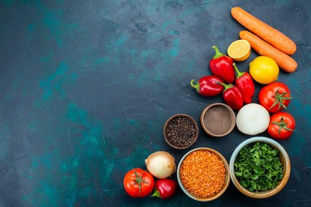 Bovenaanzicht verse groenten met greens en kruiden op het donkerblauwe bureau.