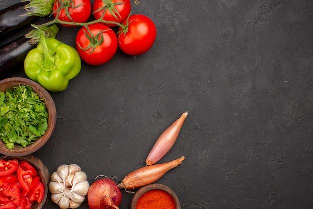 Bovenaanzicht verse groenten met greens en verschillende kruiden op donkergrijze achtergrond maaltijdsalade gezondheidsvoedsel groente