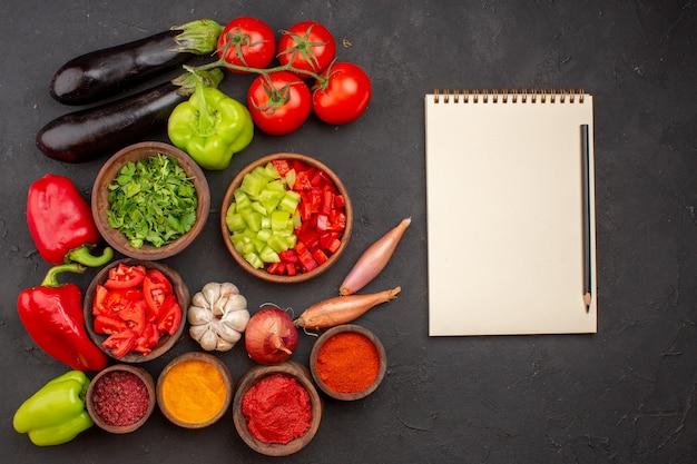 Bovenaanzicht verse groenten met greens en verschillende kruiden op grijze achtergrond maaltijdsalade gezondheidsvoedsel groenten