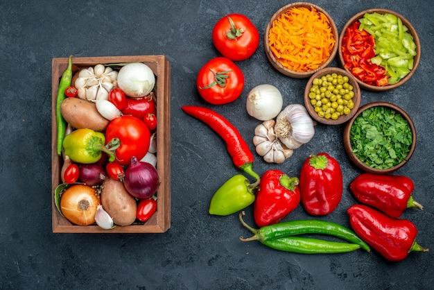 Bovenaanzicht verse groenten met knoflook op donkere tafel salade maaltijd rijpe kleuren