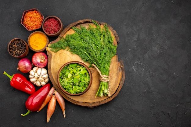 Bovenaanzicht verse groenten met kruiden en groenten op het donkere oppervlak salade gezondheid rijpe maaltijd groente