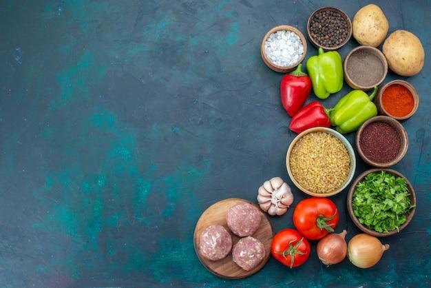 Bovenaanzicht verse groenten met kruiden, vlees en groenten op het donkerblauwe bureau