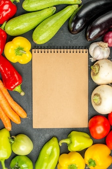 Bovenaanzicht verse groenten met notitieblok op donkere achtergrond