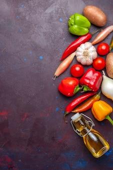 Bovenaanzicht verse groenten met olie op donkere oppervlak plantaardige maaltijd voedselolie