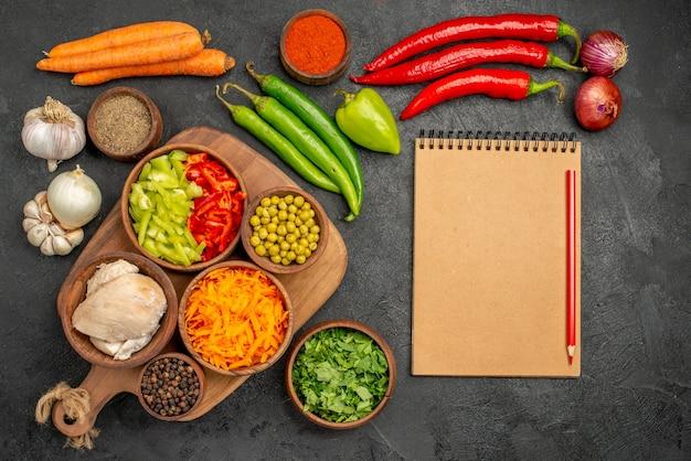 Bovenaanzicht verse groenten met peper en knoflook op donkere tafel