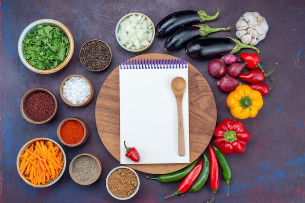 Bovenaanzicht verse groenten met salade blocnote en kruiden op donkere bureausalade maaltijd groentesnack