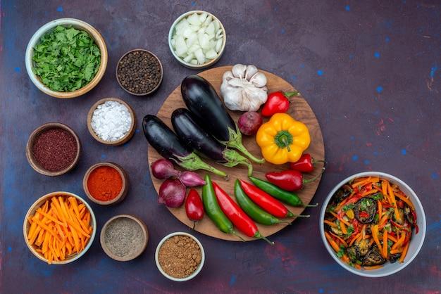 Bovenaanzicht verse groenten met salade en kruiden op het donkere bureau