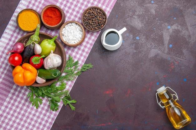Bovenaanzicht verse groenten met smaakmakers op het donkere oppervlak rijpe salade eten gezondheidslunch