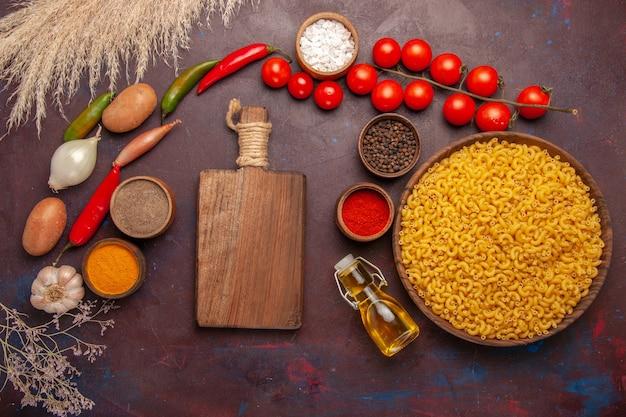 Bovenaanzicht verse groenten met verschillende kruiden en pasta op de donkere ruimte