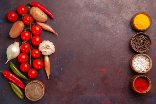 Bovenaanzicht verse groenten met verschillende kruiden op het donkerpaarse bureau