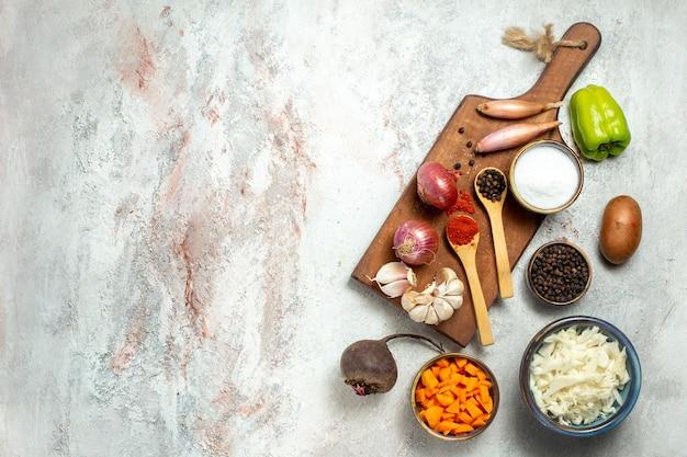 Bovenaanzicht verse groenten met verschillende smaakmakers op witruimte