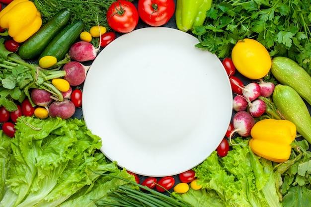 Bovenaanzicht verse groenten peterselie paprika sla dille citroen tomaten radijs witte ronde plaat op donkere ondergrond