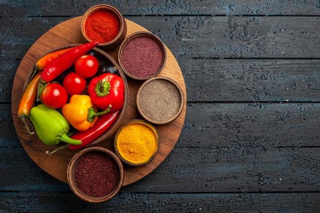 Bovenaanzicht verse groenten tomaten en peper met kruiden op donker bureau