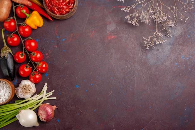 Bovenaanzicht verse groenten tomaten, uien en aardappelen op donkere ruimte