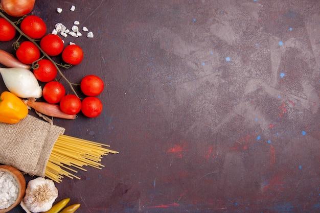 Bovenaanzicht verse groenten tomaten uien pasta en aardappelen op donkere ruimte
