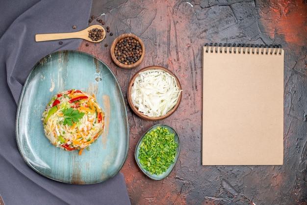 Bovenaanzicht verse groentesalade binnen bord met greens op donkere tafel