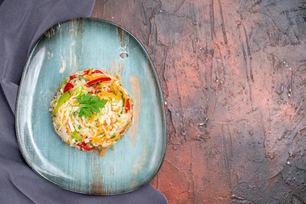 Bovenaanzicht verse groentesalade binnen bord op donkere tafel