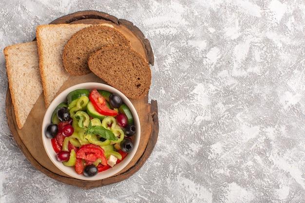 Bovenaanzicht verse groentesalade met gesneden komkommers, tomaten, olijven en witte kaas in plaat met gesneden brood op het grijze bureau