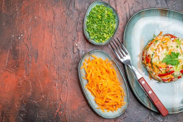 Bovenaanzicht verse groentesalade met greens op donkere tafel