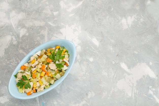 Bovenaanzicht verse groentesalade met kippenplakken in blauwe plaat op het lichtbureau plantaardig voedsel maaltijd diner vlees