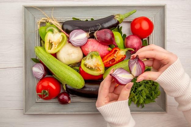 Bovenaanzicht verse groentesamenstelling met greens binnen frame op witte tafel