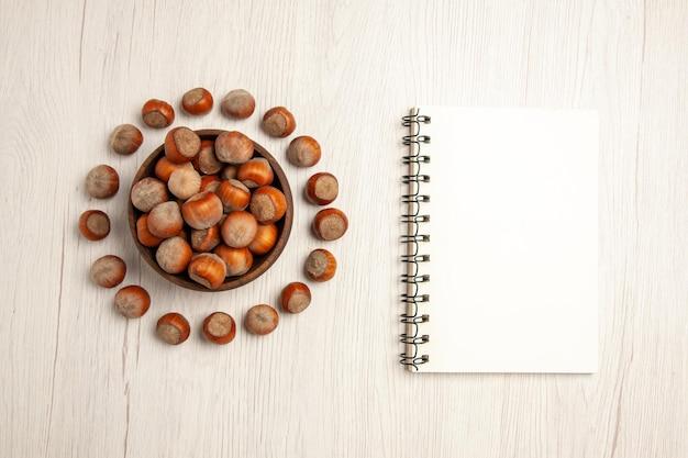 Bovenaanzicht verse hazelnoten met notitieblok op witte bureaunoot snack plant walnoot pinda
