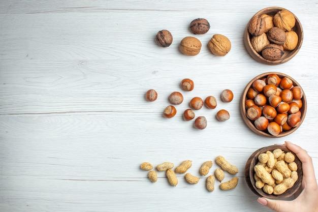 Bovenaanzicht verse hazelnoten met pinda's en walnoten op witte tafel