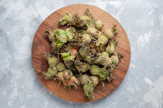 Bovenaanzicht verse hele hazelnoten met schillen op de witte hazelnoot walnoot