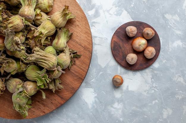 Bovenaanzicht verse hele hazelnoten met schillen op de witte vloer noten hazelnoot walnoot plant boom