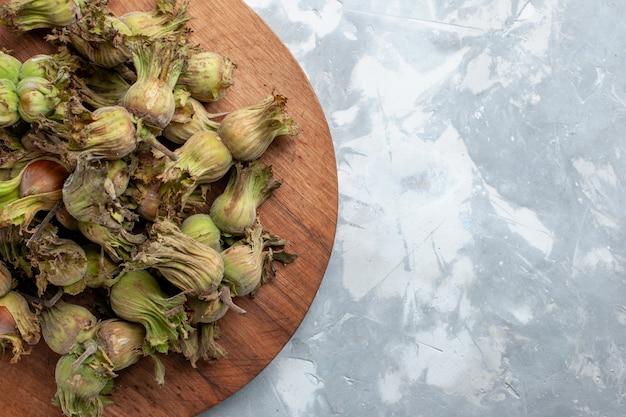 Bovenaanzicht verse hele hazelnoten met schillen op witte bureaunoot hazelnoot walnotenboom