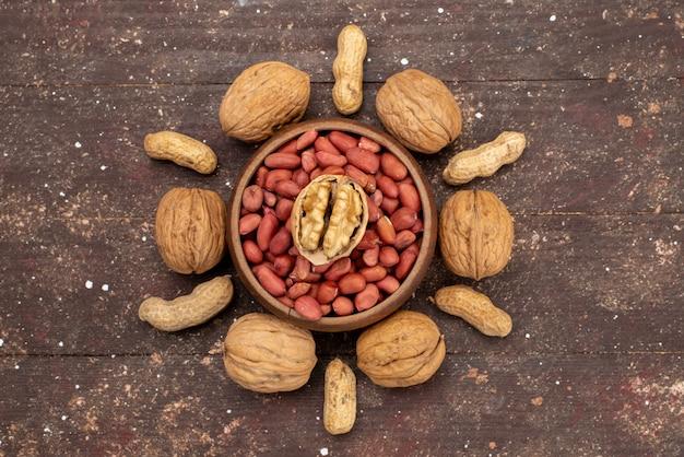 Bovenaanzicht verse hele noten walnoten en pistachenoten op bruin