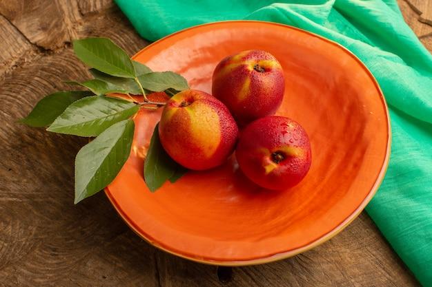 Bovenaanzicht verse hele perziken in oranje plaat op de bruine houten bureau vruchtensap zomerkleur