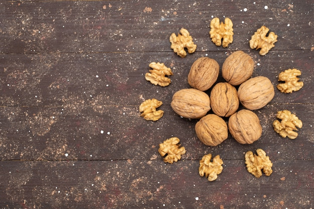 Bovenaanzicht verse hele walnoten in de schaal en schoongemaakt op bruin hout