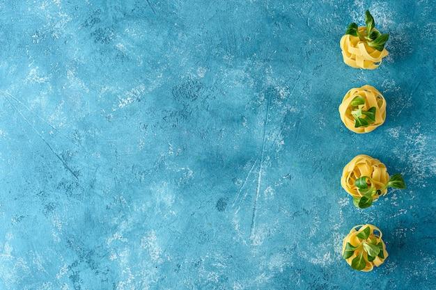 Bovenaanzicht verse italiaanse pasta, fettuccine met greens op blauwe achtergrond met kopie ruimte