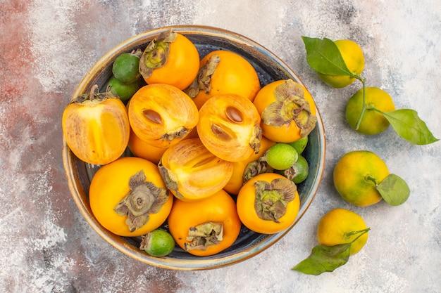 Bovenaanzicht verse kaki feykhoas in een grote kom en mandarijnen op naakte achtergrond