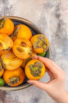 Bovenaanzicht verse kaki feykhoas in een kom persimmon in vrouwelijke hand op naakte achtergrond