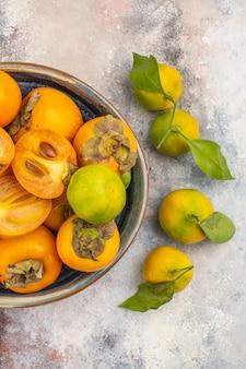 Bovenaanzicht verse kaki in een kom en mandarijnen op naakte achtergrond