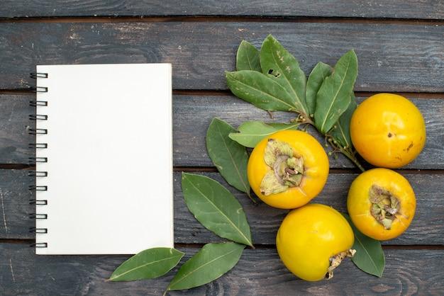 Bovenaanzicht verse kaki op houten rustieke tafel, fruit mellow rijp