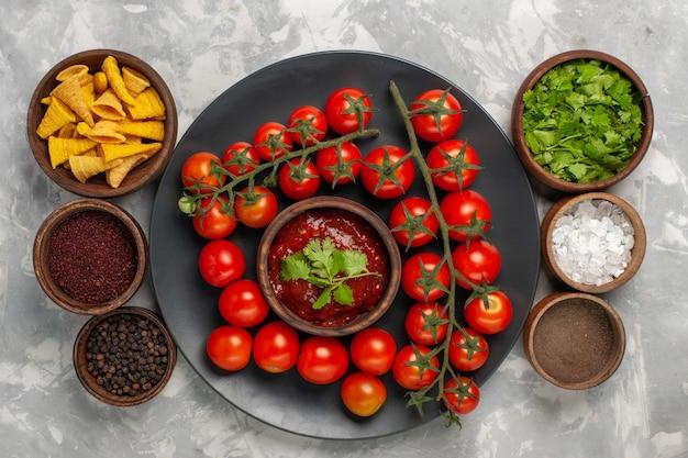 Bovenaanzicht verse kerstomaatjes in plaat met tomatensaus en kruiden op het witte oppervlak