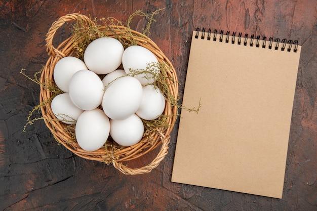 Bovenaanzicht verse kippeneieren in mand op donkere tafel