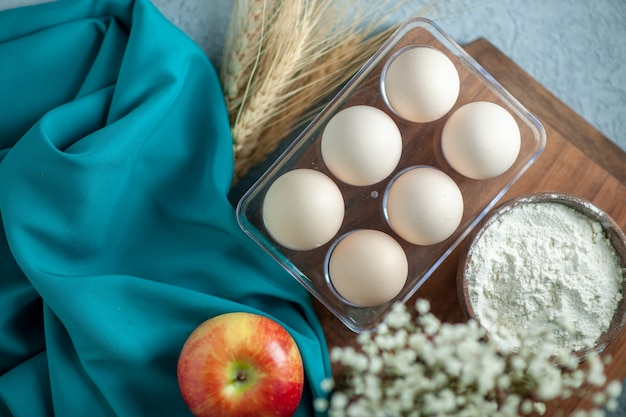Bovenaanzicht verse kippeneieren op lichte tafel thee dessert taart suiker fruit koekje koekje zoete cakedeeg