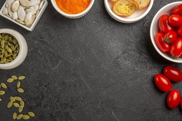 Bovenaanzicht verse kleine tomaten met zaden en geplette pompoen op de grijze achtergrond zaad rijpe kleur