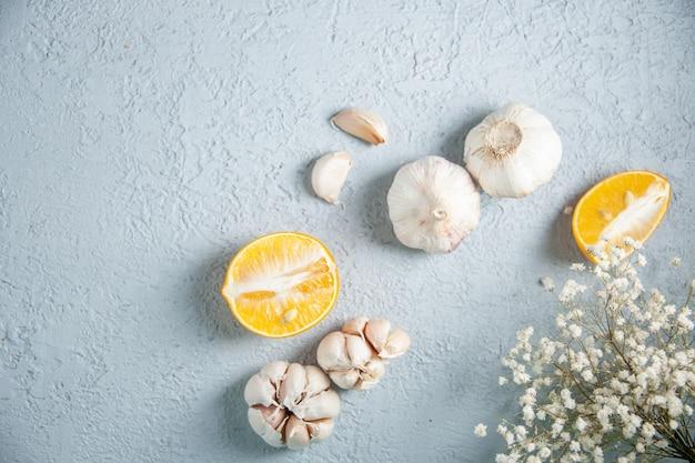 Bovenaanzicht verse knoflook met citroen op lichte achtergrond voedsel plant plantaardige peper zure kruiden