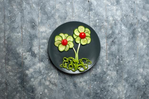 Bovenaanzicht verse komkommers bloem ontworpen salade op grijze ruimte