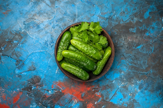 Bovenaanzicht verse komkommers in plaat op blauwe achtergrond foto kleur rijp salade eten maaltijd