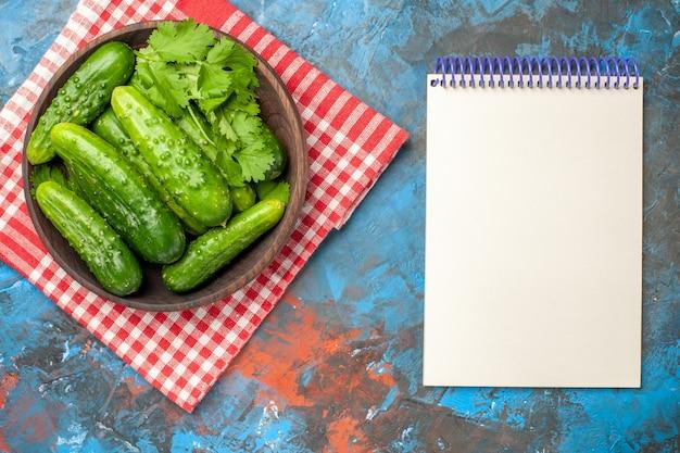 Bovenaanzicht verse komkommers in plaat op blauwe achtergrond salade gezondheid foto rijpe maaltijd voedselkleur